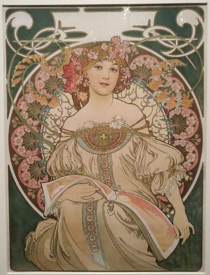 Affiche réalisée par Mucha, on y voit une femme couronnée de fleurs.