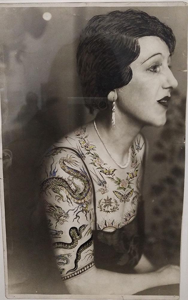 Il s'agit d'une Photographie de mode, vers 1935. L'épreuve a été rehaussée de couleurs. Cette photo est conservée dans une collection particulière. Elle représente une femme avec des motifs peints sur la peau ressemblant à des tatouages. Ces tatouages ont été peints après tirage de la photo.