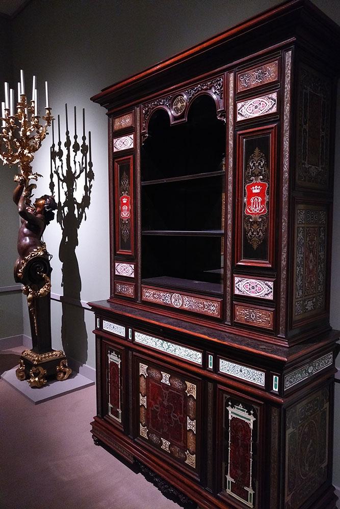On voit un porte-flambeau au motif de femme nue et une grande armoire de type Boulle.