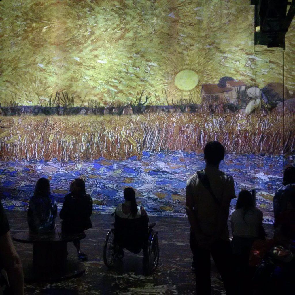 Projection d'une œuvre de van Gogh avec le public devant en train de regarder.