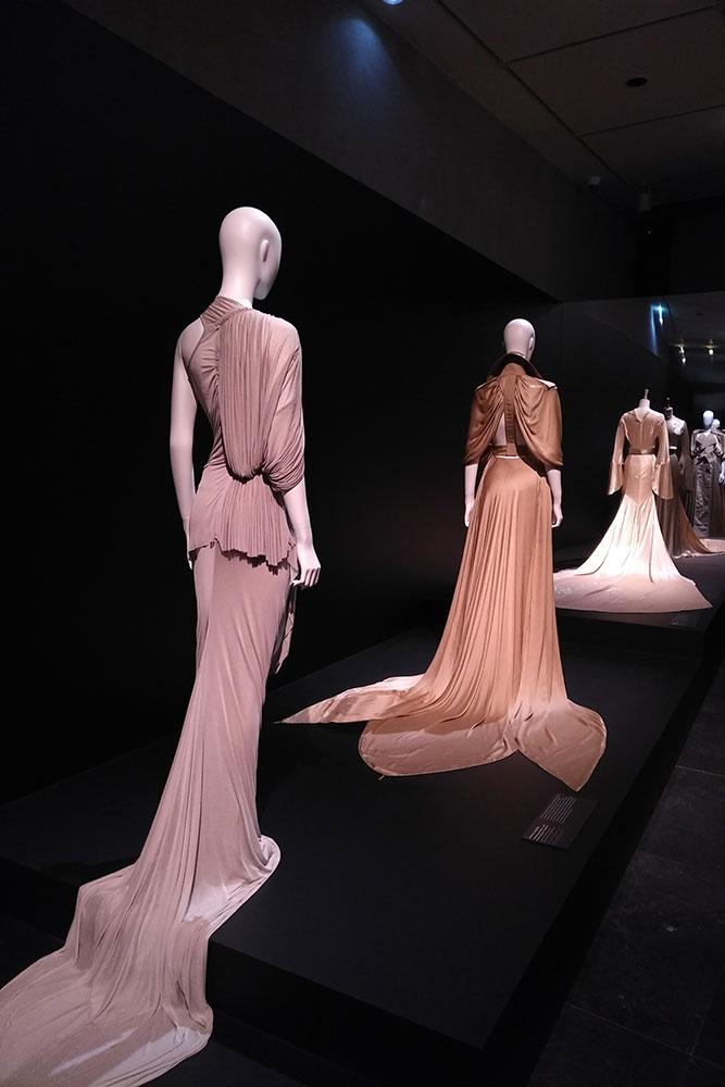 L'image montre trois mannequins portant des robes agrémentées de traîne.