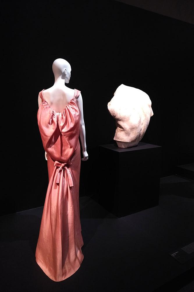 On peut voir un mannequin portant une longue robe rose faite par Balenciaga et à côté un torse d'homme sculpté par Bourdelle.