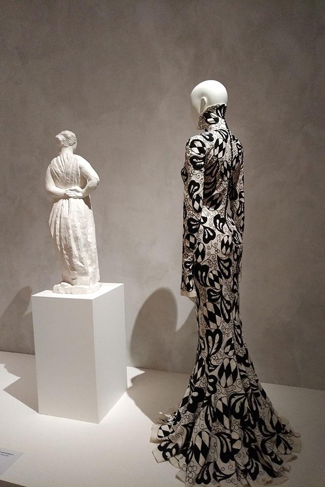Cette robe fourreau est mise sur un mannequin à côté d'une sculpture de Bourdelle. La robe est longue et couvre tout le corps, elle imite les robes du 19e siècle.